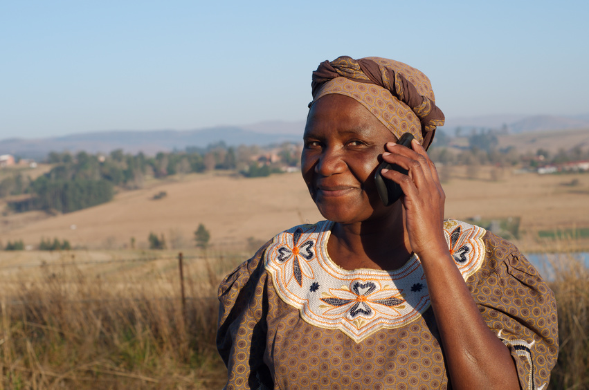 Traditional African Zulu woman speaking on mobile cell phone telephone in rural KwaZulu-Natal.